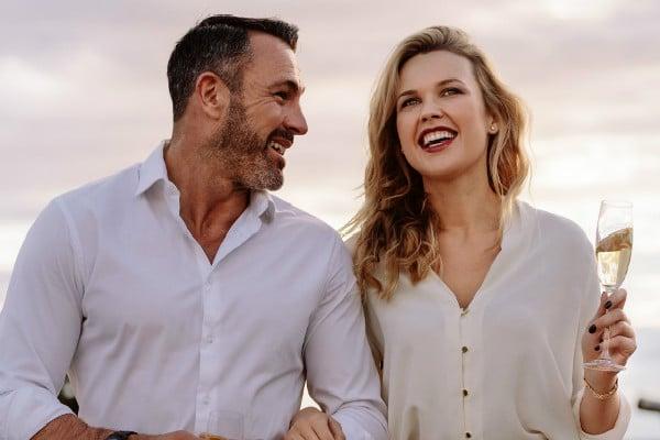 Jolie fille rit avec un homme mûr pendant qu'ils boivent du champagen