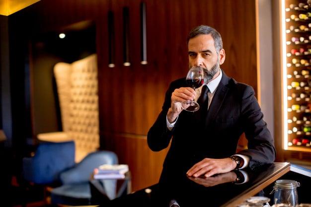 Beau et beau homme mûr boit du vin